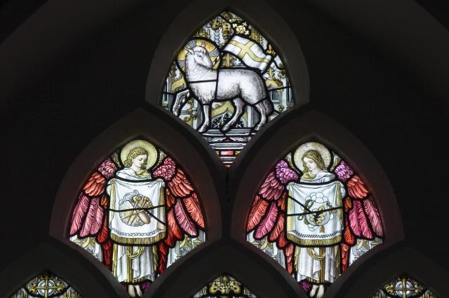 Tracery Lights depicting the Agnus Dei, and Angels Showing Banners Bearing the Intruments of the Pas    detail from    The Crucifixion